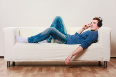 Young man with headphones lying on couch Royalty Free Stock Images