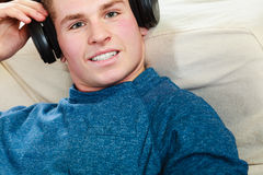 Young man with headphones lying on couch Stock Photos