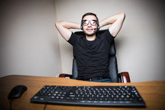 Young man with headphones playing computer games in dark room Royalty Free Stock Photo
