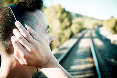 Young man with headphones at the railroad tracks Stock Images
