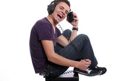 Young man with headphones, seating in a speaker. Isolated in white background royalty free stock photography