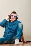 Young man with headphones sitting on floor Royalty Free Stock Images