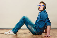 Young man with headphones sitting on floor Royalty Free Stock Photography