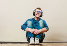 Young man with headphones sitting on floor Royalty Free Stock Image
