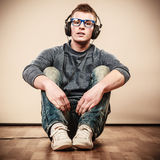 Young man with headphones sitting on floor Royalty Free Stock Photo