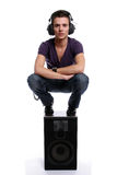 Young man with headphones, stading in a speaker. Isolated in white background stock image