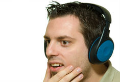 Young man with headphones surprised. A man, wearing headphones, listening to music, looking surprised Royalty Free Stock Photo