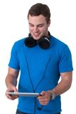 Young man with headphones working on a tablet pc Stock Image