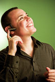 Young man on headset. Young man on wireless cellular phone headset with happy smiling expression. Green background Royalty Free Stock Photo