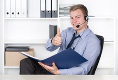 Young man with headset and file holds thumb up Stock Photos
