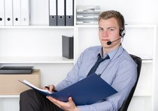 Young man with headset and file in the office Royalty Free Stock Photography