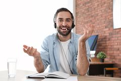 Young man with headset looking at camera and using video chat royalty free stock photo