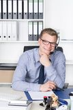 Young man with headset is sitting at his desk Royalty Free Stock Images