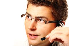 Young man with headset talking. Young handsome worker with headset talking to a customer over white background Stock Photography