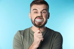 Young man with healthy teeth and magnifier. On color background royalty free stock image
