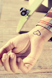 Young man with a heart in his wrist, outdoors Royalty Free Stock Photography