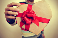 Young man with a heart-shaped gift Stock Image
