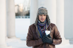 Young man with a heart shaped snowball Royalty Free Stock Image