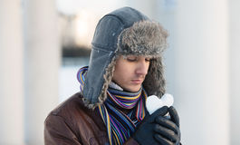 Young man with a heart shaped snowball Stock Photos