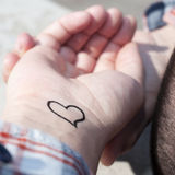 Young man with a heart ttatooed in his wrist Royalty Free Stock Images