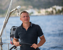 Young man at the helm of a sailing yacht. Sport. Royalty Free Stock Image