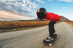 A young man in helmet and a leather suit in a special rack rides a longboard on afsaltu on background mountains and. A young man in a fullface helmet and a Stock Photos