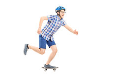 Young man with helmet riding a small skateboard Royalty Free Stock Images