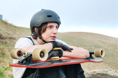 A young man in a helmet wearing gloves with a board in his hands and dressed is sitting on a precipice high in the Stock Photo