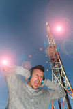 Young Man with Helmets and Telecommunications Antenna between. Young Man with Headphones sound or music, with expression of receiving a brutal volume, surrounded Royalty Free Stock Image