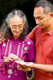 Young man help elderly mother taking medicine. Asian ethnic senior women taking pills helped by young adult son Stock Photography