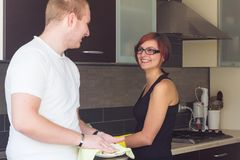 Young man helping girlfriend to do dishes Stock Photos