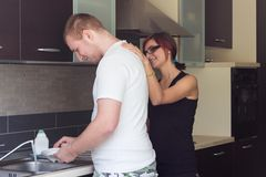 Young man helping girlfriend to do dishes Royalty Free Stock Images