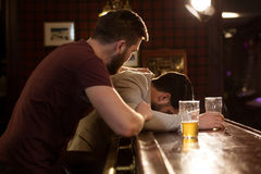 Young man helping his drunk friend Royalty Free Stock Photography