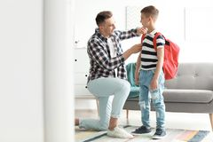 Young man helping his little child get ready for school. Young men helping his little child get ready for school at home royalty free stock images