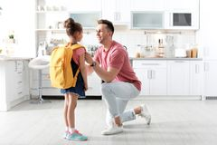 Young man helping his little child get ready for school royalty free stock image