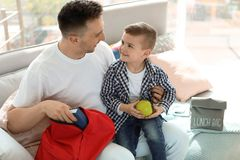 Young man helping his little child get ready for school. Young men helping his little child get ready for school at home Royalty Free Stock Photo