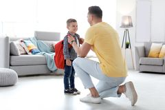 Young man helping his little child get ready for school. Young men helping his little child get ready for school at home royalty free stock photography