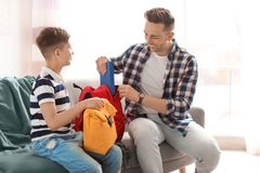 Young man helping his little child get ready for school. Young men helping his little child get ready for school at home stock images
