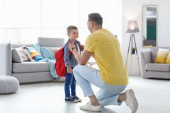 Young man helping his little child get ready. Young men helping his little child get ready for school at home stock images