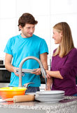 Young man helping his wife in household stock photography