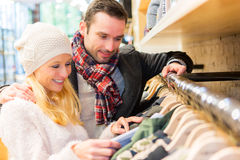 Young man helping his wife to choose clothes Royalty Free Stock Image