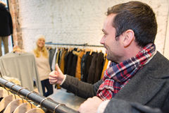 Young man helping his wife to choose clothes Stock Image