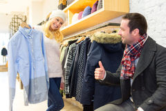 Young man helping his wife to choose clothes Stock Images