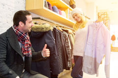 Young man helping his wife to choose clothes Royalty Free Stock Images