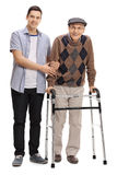 Young man helping a mature man with a walker Royalty Free Stock Photos
