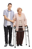 Young man helping a mature woman with a walker. Full length portrait of a young men helping a mature women with a walker isolated on white background Royalty Free Stock Image