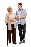 Young man helping a mature woman with a walking cane Stock Image