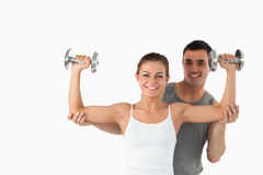 Young man helping a smiling woman to work out stock images