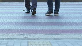 Young man helping to blind man with cane to cross road, assistance and kindness. Stock footage stock video footage