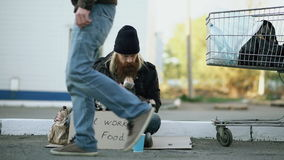 Young man helps to homeless person and giving him some food while beggar drink alcohol and sit near shopping cart at. The street stock video footage